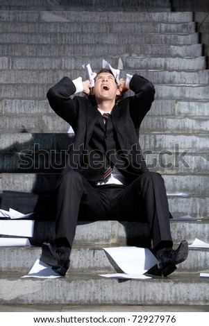 Despaired businessman screaming with papers in hands while sitting on staircase - stock photo