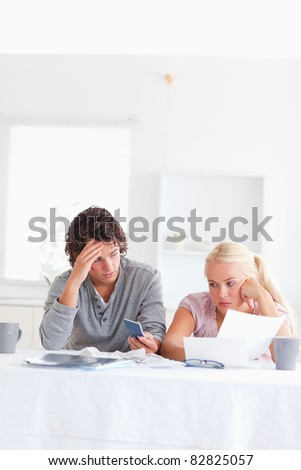 Despaired couple calculating in their living room - stock photo