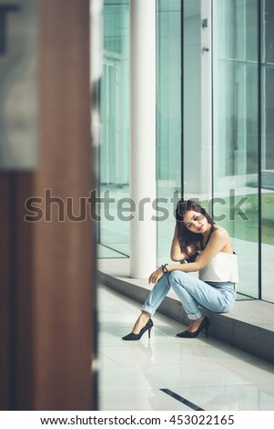 despaired girl sit on edge of glass window wall