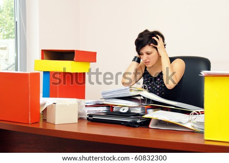 despaired stressed woman sitting at desk overloaded with work holding her head