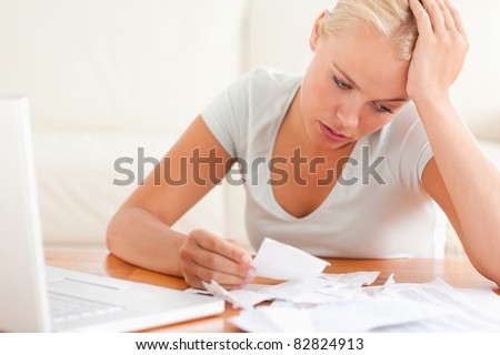 Despaired woman accounting in the living room - stock photo