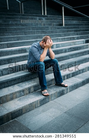 Despaired young man covering his face with hands sitting on stairs of big building. Feelings of sadness, despair and tragedy - stock photo