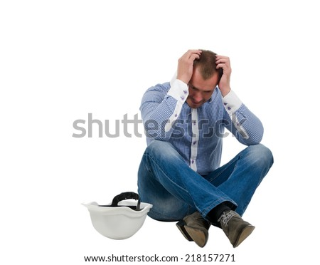 Despairing architect, builder or structural engineer sitting cross legged on the floor with his hardhat alongside him and head in his hands , isolated on white - stock photo