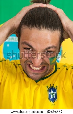 Despairing Brazilian sports fan, watching his national team fail in an important game - stock photo