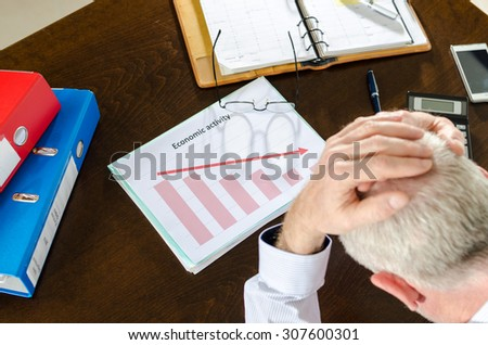 Despairing businessman because of the economic crisis - stock photo