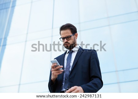Despairing businessman reading text message while holding mobile phone - stock photo