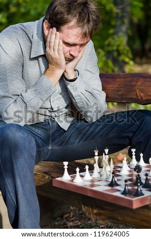 Despairing man with his chin resting in his hands looking at a chessboard as he realises his opponent is winning the game - stock photo