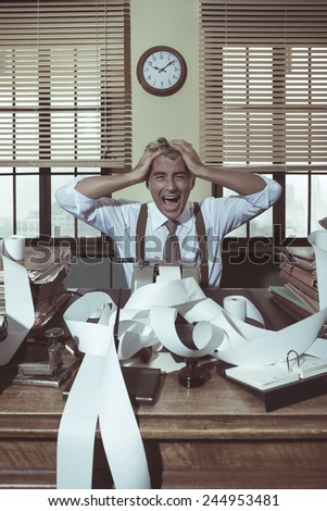 Desperate accountant shouting head in hands in vintage 1950s style office. - stock photo