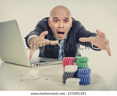 desperate addict businessman on computer laptop loosing lots of money betting on internet poker with cards and chips on online gambling addiction isolated on clear background - stock photo