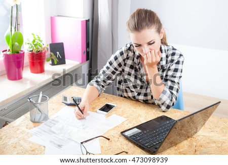 Desperate and worried young woman calculating bills in home office