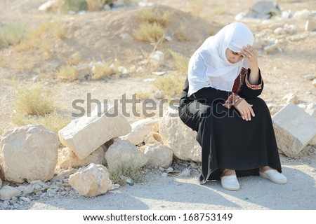 Desperate Arabic woman sitting on rock and crying - stock photo