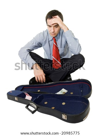 Desperate bankrupt businessman sitting by a violin case and a few coins - isolated - stock photo