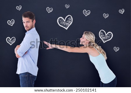 Desperate blonde reaching for boyfriend against blackboard - stock photo