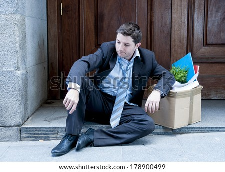 desperate business man in stress fired from job sitting on edgy street corner with office belongings in cardboard box and asking for help - stock photo