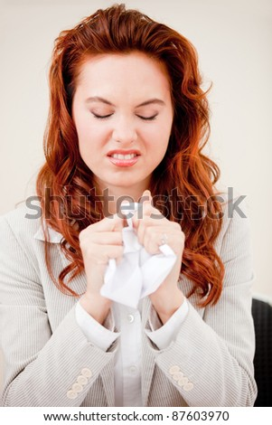 Desperate business woman crumpling paper and looking upset - stock photo