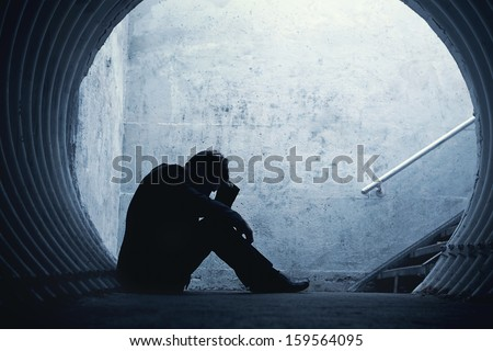 Desperate Businessman in silhouette lying on the ground and holding his head in a dark tunnel. With room for your text - stock photo