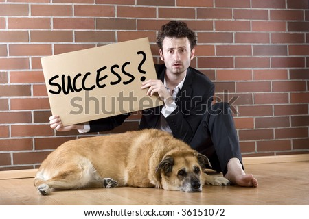 "desperate  businessman sits with a dog on the floor and holds a ""Success"" sign - stock photo"
