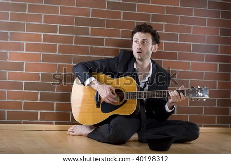desperate businessman sits with a guitar on the floor and sings fort money - stock photo