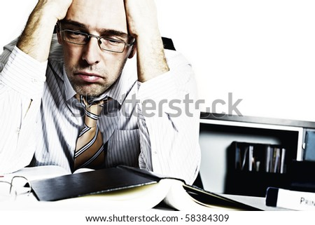 Desperate businessman sitting at desk in office being overloaded with loads of work - stock photo