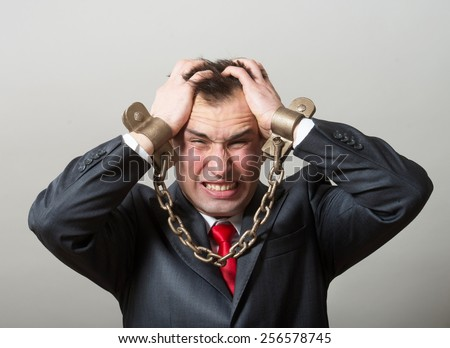 Desperate businessman with chained hands - stock photo