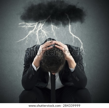 Desperate businessman with cloud over his head - stock photo