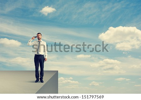desperate businessman with gun standing on the edge - stock photo