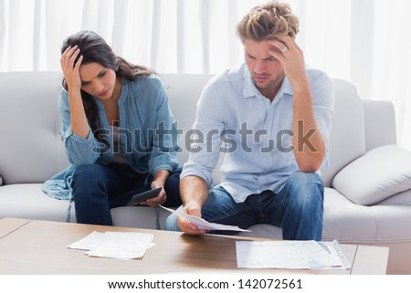 Desperate couple doing their accounts in the living room - stock photo