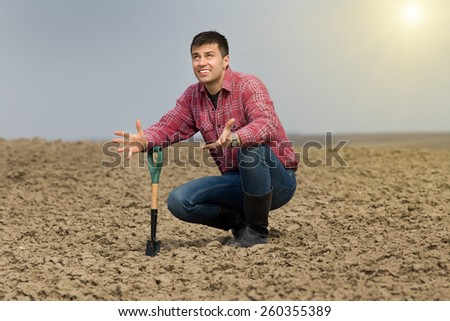 Desperate farmer holding shovel on farmland and looking in sky - stock photo