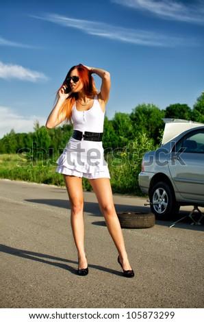 Desperate girl calling to car repair service - stock photo