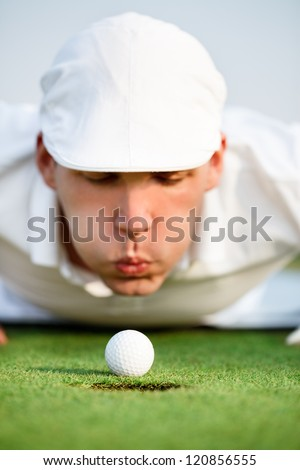 Desperate golfer blowing on golf ball to put in hole, funny golfing cheat - concept - stock photo