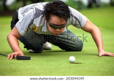 Desperate golfer blowing on golf ball to put in hole, Funny golfing cheat concept - stock photo
