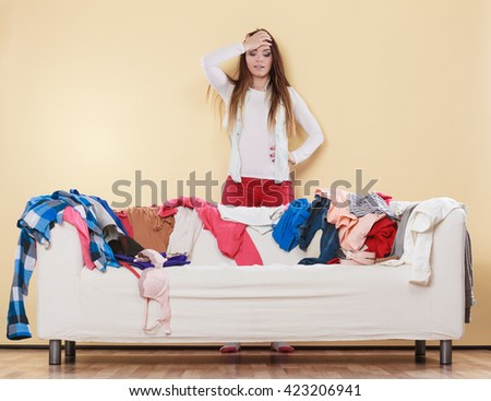 Desperate helpless woman standing behind sofa couch in messy living room with hand on head. Young girl surrounded by many stack of clothes. Disorder and mess at home. - stock photo