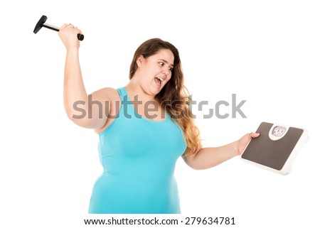 Desperate large girl punishing a weight scale with a hammer isolated in white - stock photo