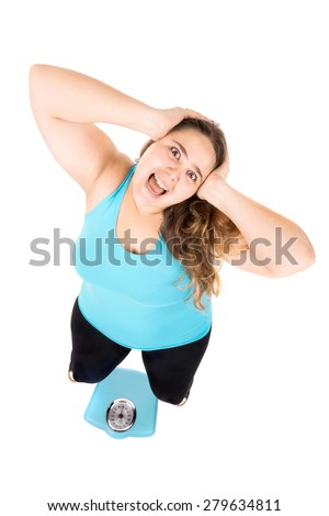Desperate large girl screaming with a weight scale isolated in white - stock photo