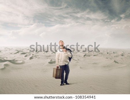 Desperate man carrying a suitcase in a desert - stock photo