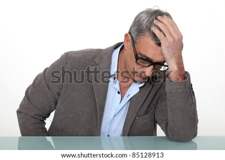 Desperate man sitting at a desk - stock photo