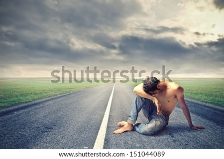 desperate man sitting shirtless in the middle of a deserted road - stock photo