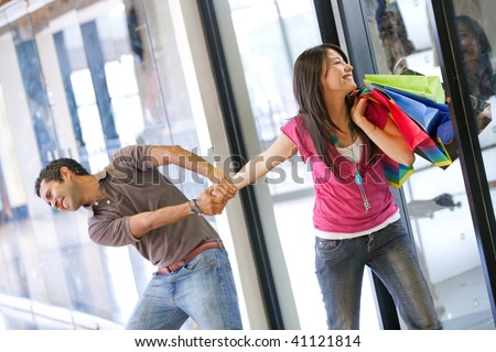desperate man trying to take his girlfriend out of a retail store - stock photo