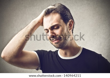 desperate man with hand in hair - stock photo