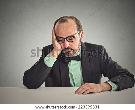 Desperate middle aged businessman sitting leaning on a desk looking down - stock photo