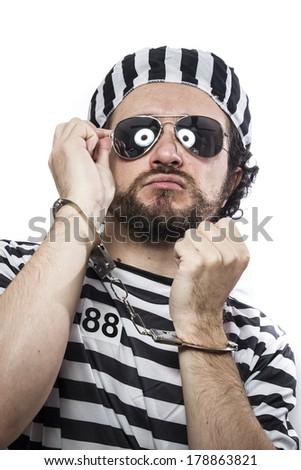 Desperate, portrait of a man prisoner in prison garb, over white background - stock photo