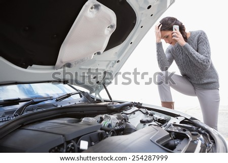 Desperate woman calling for assistance after breaking down - stock photo