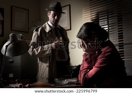Desperate woman crying head in hands and confident detective standing in his office. - stock photo