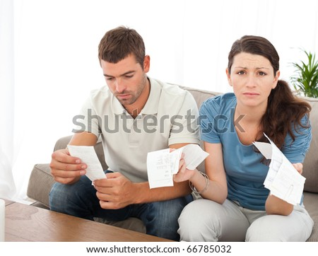 Desperate woman doing her accounts with her boyfriend sitting on the sofa at home - stock photo