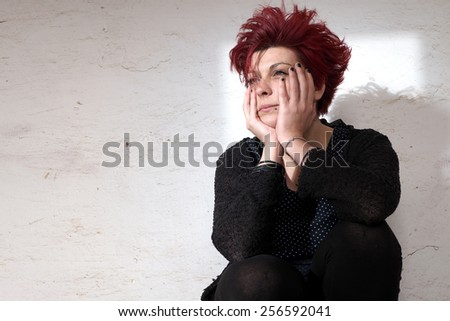 Desperate woman sitting against white wall - stock photo