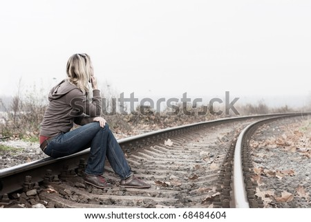 Desperate woman sitting on the railroads. - stock photo