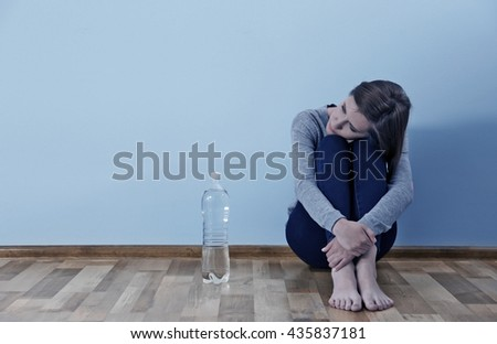 Desperate woman suffering from eating disorder on grey wall background