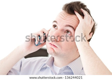 Desperate young brown-haired businessman get bad news heavy problems, faces challenges snort and holding his head while talking on the mobile phone on white isolated background - stock photo