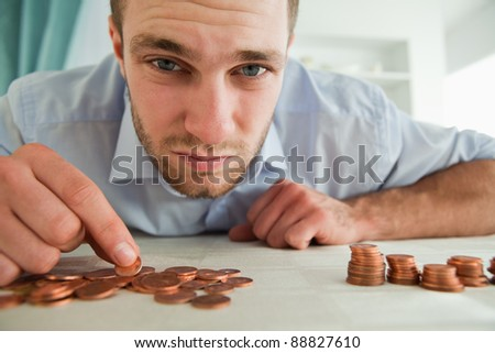 Desperate young businessman counting his change - stock photo