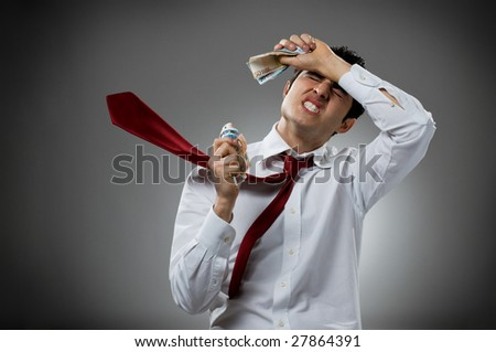 Desperate young businessman with blowing necktie and his bunch of money. Recession and crisis concept! - stock photo